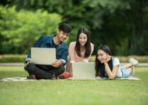 3 students studying outside with their laptops applying for a National Insurance Number